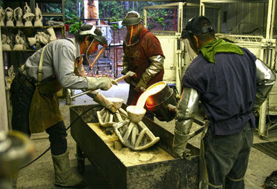 Pouring bronze into ceramic shelfs at the Maiden Foundry